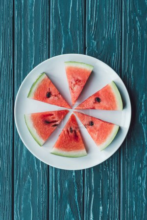 top view of arrangement of juice watermelon pieces on plate on blue wooden tabletop