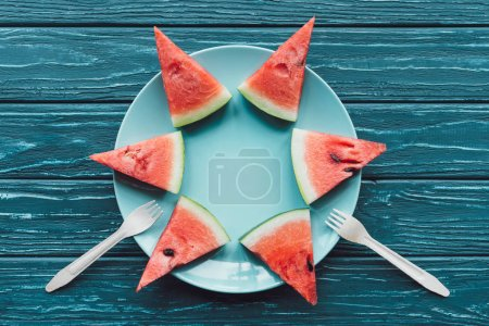 flat lay with arranged watermelon pieces on plate and plastic forks on blue wooden surface