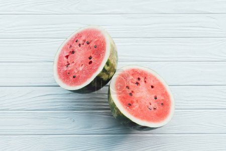 Photo for Top view of fresh watermelon halves on white wooden surface - Royalty Free Image