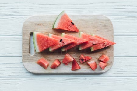 flat lay with arranged watermelon pieces on cutting board on wooden tabletop