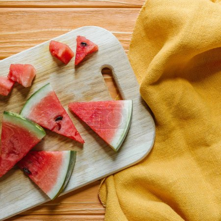 Photo for Flat lay with watermelon pieces on cutting board on wooden surface with linen - Royalty Free Image