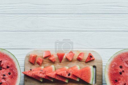 Photo for Flat lay with arranged watermelon pieces on cutting board on wooden tabletop - Royalty Free Image