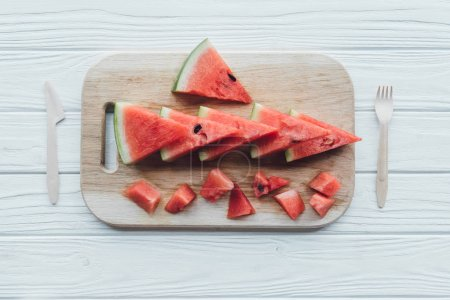 Photo for Flat lay with arranged watermelon pieces on cutting board and plastic cutlery on wooden tabletop - Royalty Free Image