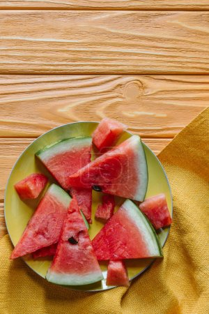 flat lay with watermelon pieces on plate on wooden tabletop with linen