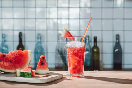 close up view of watermelon drink in glass and pieces of fresh watermelon on cutting board in cafe