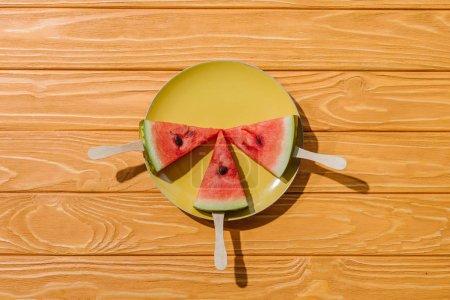 Photo pour Lay plat avec pastèques sur les bâtonnets de crème glacée sur la plaque sur le dessus de table en bois - image libre de droit