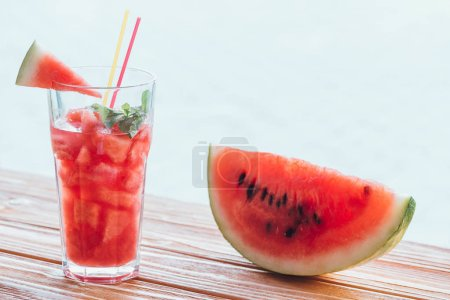 Photo for Close up view of  refreshing watermelon drink with mint in glass and slice on watermelon on wooden surface - Royalty Free Image