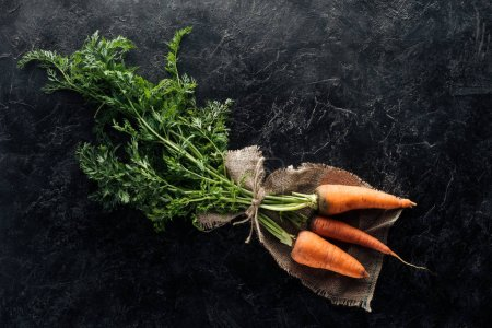 Photo for Top view of fresh ripe carrots tied with rope on sackcloth on black marble surface - Royalty Free Image