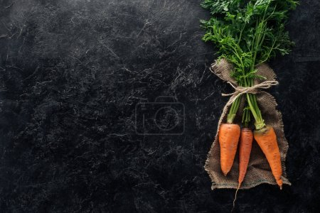 top view of fresh ripe carrots tied with rope on sackcloth on black marble surface