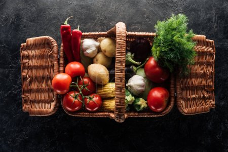flat lay with various fresh vegetables in basket on black marble tabletop