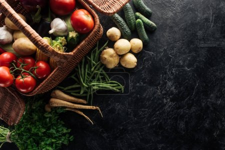 Photo for Flat lay with various fresh vegetables in basket on black marble tabletop - Royalty Free Image