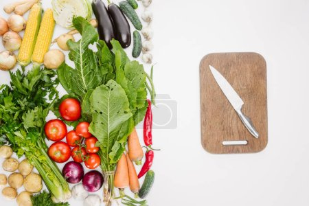 flat lay with ripe autumn vegetables and wooden cutting board with knife isolated on white