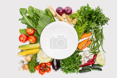 top view of food composition with fall harvest with empty plate in middle isolated on white