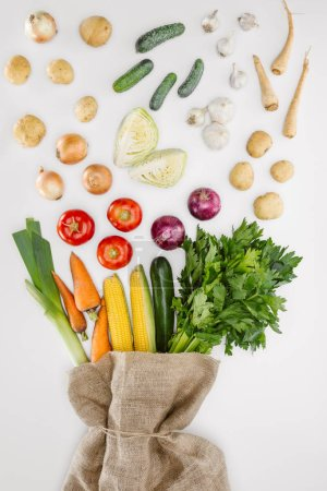 top view of fresh raw vegetables and sackcloth arranged isolated on whit