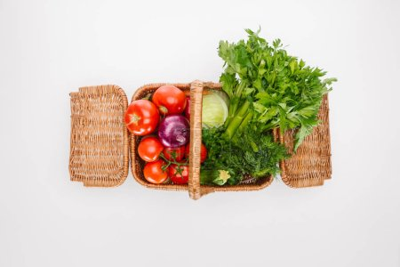 top view of raw autumn vegetables in basket isolated on white