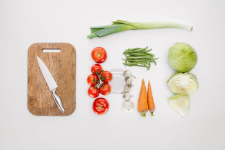 top view of ripe vegetables and cutting board with knife isolated on white