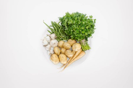 top view of arranged ripe vegetables on plate isolated on white