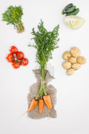 flat lay with carrots on sackcloth and vegetables arranged around isolated on white