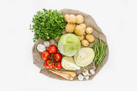 Photo for Food composition with fresh vegetables arranged on sackcloth isolated on white - Royalty Free Image