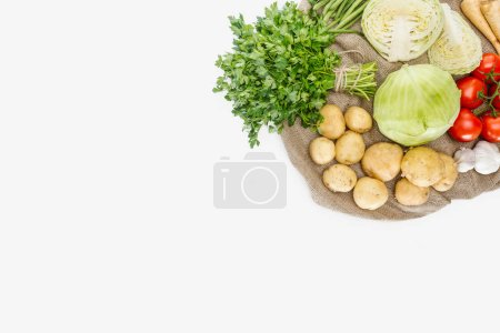 top view of arranged seasonal ripe vegetables on sackcloth isolated on white
