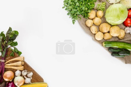 top view of arranged raw vegetables on wooden cutting board and sackcloth isolated on white