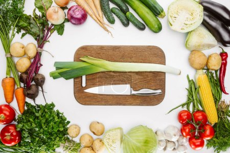 top view of ripe vegetables and cutting board with knife and leek isolated on white