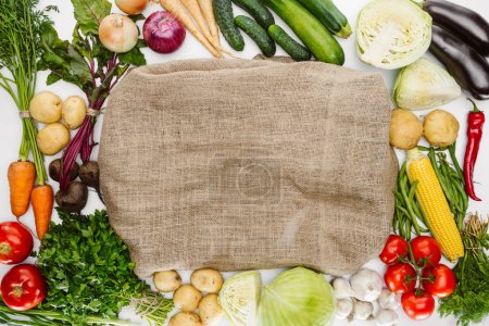 food composition with ripe vegetables arranged around sackcloth isolated on white