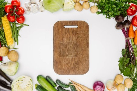 flat lay with ripe autumn vegetables and empty wooden cutting board isolated on white