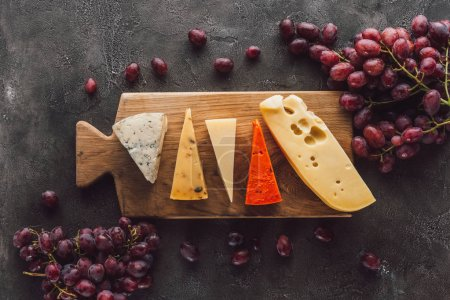 Photo for Top view of assorted cheese on wooden cutting board with grape on dark surface - Royalty Free Image