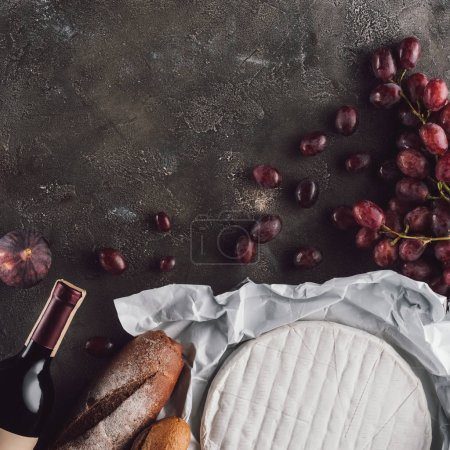 flat lay with food composition of bread loafs, camembert cheese and bottle of wine on dark surface
