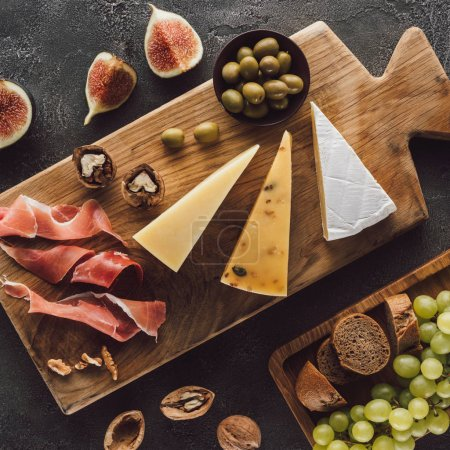 flat lay with assorted cheese, jamon and fruits on dark surface