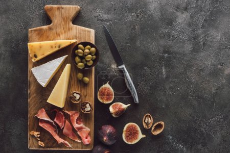 Photo for Flat lay with assorted cheese, jamon and figs on dark surface - Royalty Free Image
