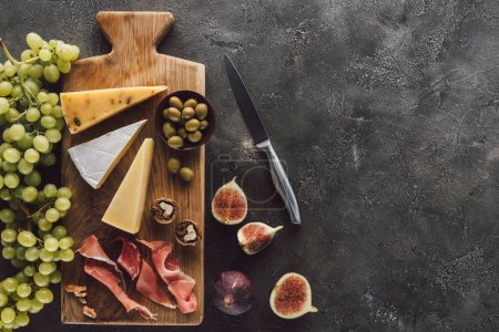 Photo for Flat lay with assorted cheese, jamon, grape and figs on dark surface - Royalty Free Image