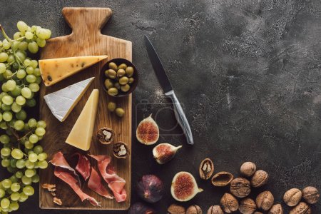 flat lay with assorted cheese, jamon, grape, hazelnuts and figs on dark surface