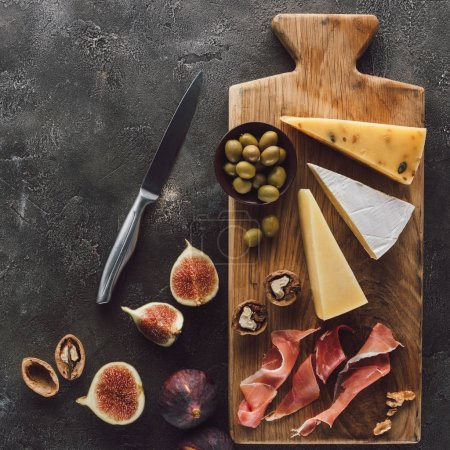 flat lay with assorted cheese, jamon, olives and figson dark surface