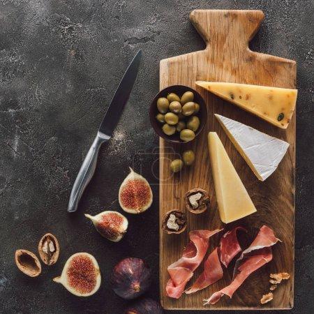 flache Lage mit verschiedenen Käsesorten, Marmelade, Oliven und Feigen dunkle Oberfläche