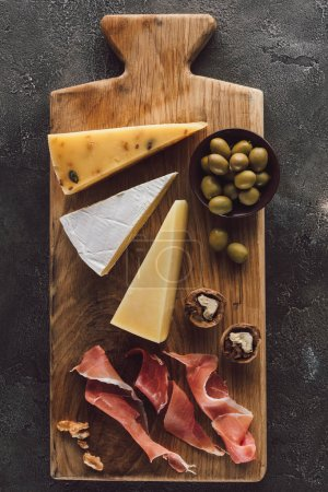 flat lay with assorted cheese, jamon and olives in bowl on dark surface