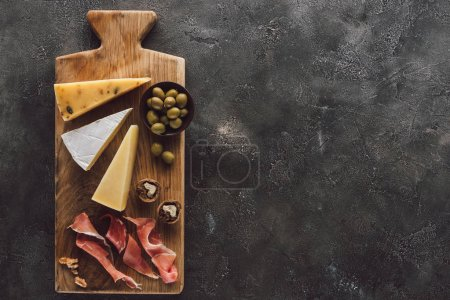 Photo for Flat lay with assorted cheese, jamon and olives in bowl on dark surface - Royalty Free Image