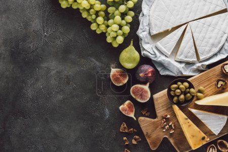 Photo for Top view of assorted cheese, olives and fruits on dark tabletop - Royalty Free Image