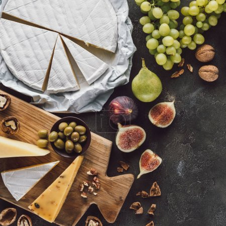 top view of assorted cheese, olives in bowl and fruits on dark tabletop