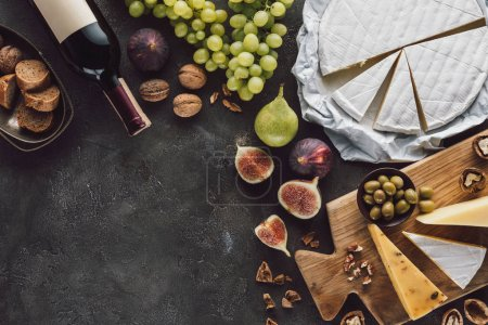 Photo for Top view of assorted cheese, bottle of wine and fruits on dark tabletop - Royalty Free Image