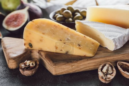 close up view of cheese assorted on wooden cutting board with hazelnuts and olives on dark surface