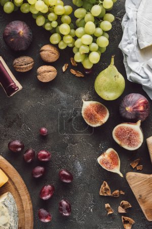 Photo for Flat lay with arranged fruits, cheese and hazelnuts on dark surface - Royalty Free Image