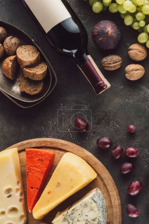 food composition with bottle of wine, grape, bread pieces and assorted cheese on dark surface