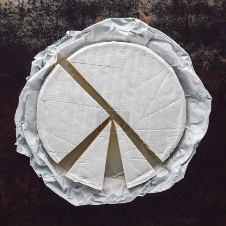 top view of cut camembert cheese on dark surface