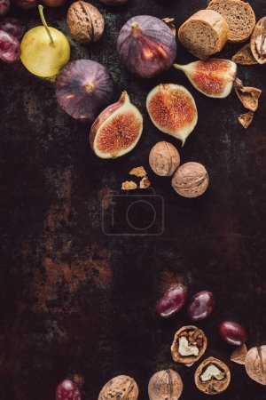 food composition with assorted bread, fruits and hazelnuts on dark surface