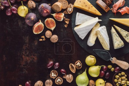 flat lay with assorted cheese, hazelnuts and fruits on dark surface