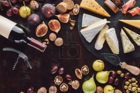 Photo for Flat lay with assorted cheese, bottle of wine and fruits on dark surface - Royalty Free Image