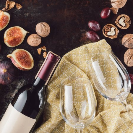 top view of bottle of wine, empty glasses, hazelnuts and figs on dark tabletop