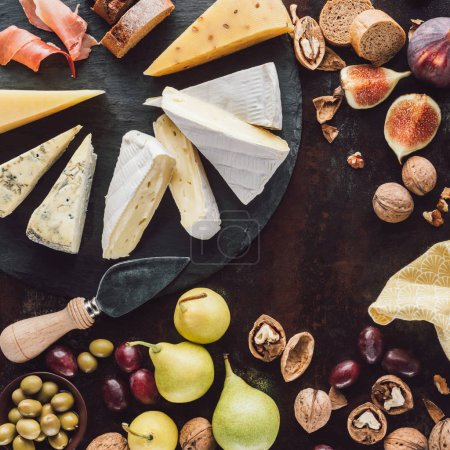 flat lay with assorted cheese, olives in bowl and fruits on dark surface